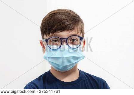Child In A Medical Mask. Close-up Portrait With A Surgical Mask On Face Isolated On White Background