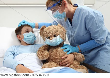 Nurse Takes Care Of The Patient Child In Hospital Bed Playing With Teddy Bear, Wearing Protective Ma