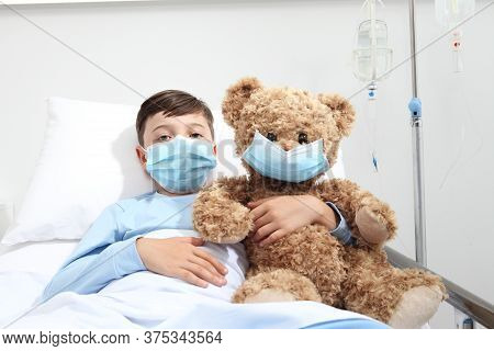 Child In Hospital Bed With Teddy Bear Wearing Protective Mask, Corona Virus Covid 19 Protection Conc