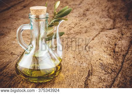 Extra Virgin Olive Oil In Rustic Bottle On Old Wooden Table, Blank Space.