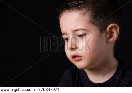 Portrait Of A Sad Jung Boy Isolated On Black