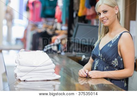 Smiling woman behind counter with folded clothes