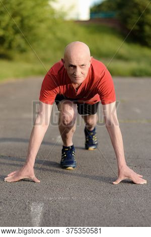 Senior Man In Position Ready To Run. Determined Man Ready For A Sprint. Health Lifestyle And Exercis