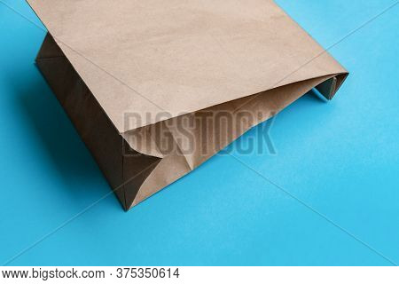 Simple Brown Paper Bag For Lunch Or Food On Table. Craft Paper Bag On Bright Blue Background. Zero W