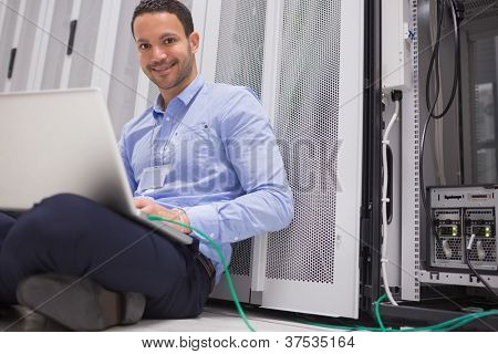 Happy technician working on laptop connected to server in data center