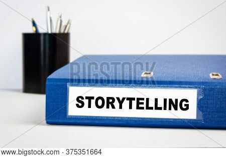 Storytelling - The Name Of The Folder Is A Registrar In Blue On A Table In An Office With A Pencil B