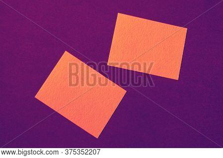 Orange Paper Cards On Purple Background Arranged In Random Manner, Ad Mockup In Bright Intense Vibra