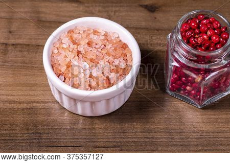 Closeup On Bowl With Pink Himalayan Salt And Glass Jar With Red Peppercorns