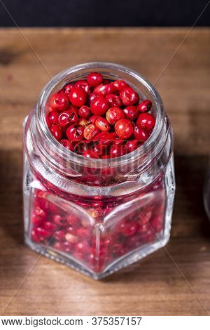 Closeup In Glass Jar With Grains Of Red Pepper On Wooden Background