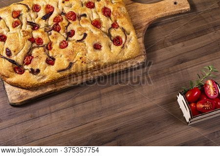 Traditional Italian Focaccia With Cherry Tomatoes, Black Olives And Rosemary.