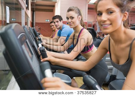 Four people working out on exercise bikes in gym