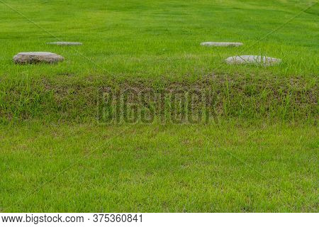 Four Round Stones On Mound Of Archeological Site In Buyeo, South Korea.