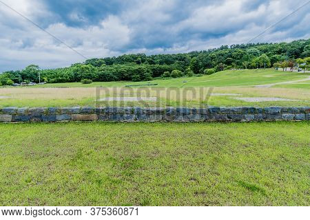 Landscape Of Archeological Site In Buyeo, South Korea With Forest And Cloudy Sky In Background.