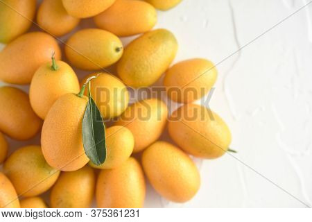 Fresh Kumquats, Small Exotic Citrus Fruits, On A White Textured Background. Top View With Copy Space