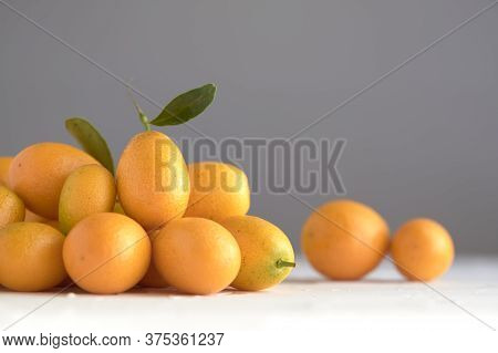 Fresh Kumquats, Small Exotic Citrus Fruits, On A White Textured Surface, Gray Background