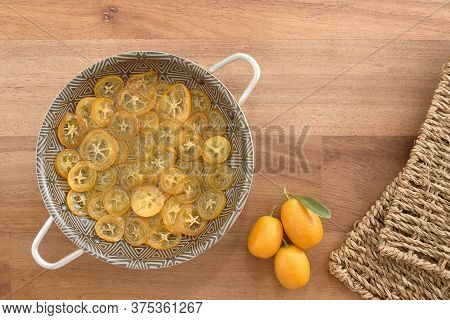 Candied And Sliced Kumquats In A Pan And Other Fresh Ones, On A Wooden Base. Top View.