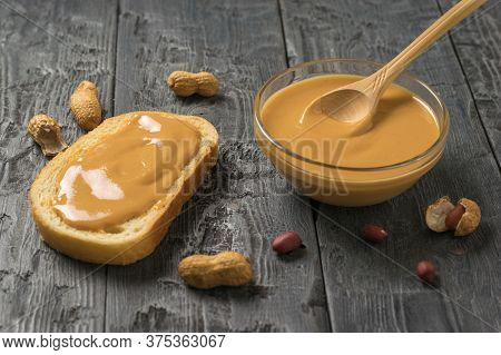 Peanut Paste In A Bowl And On A Piece Of Bread On A Wooden Table. Natural Peanut Cream.