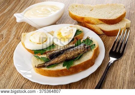 Bowl With Mayonnaise, Slices Of Wheat Bread, Sandwiches With Sprats, Boiled Eggs And Parsley In Whit