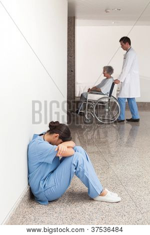 Nurse sitting on the ground in the hallway of the hospital with head in hands
