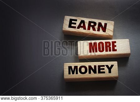 Earn More Money Written On A Wooden Blocks On Black. Business Career Concept