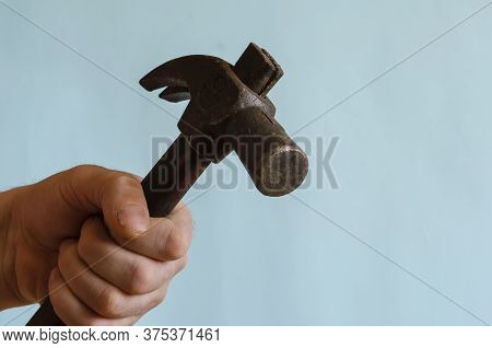 Close-up Of A Male Hand Striking With A Hammer. Male Hand With A Hammer With A Long Wooden Hilt. Mid