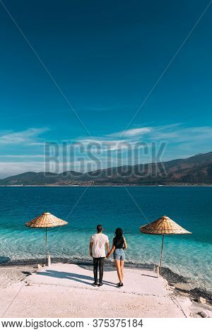 Couple On The Beach Rear View. Honeymoon Lovers. Man And Woman On The Island. Couple In Love On Vaca
