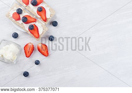 Cooking Of Healthy  Dietary Sandwiches Of Dry Crisps Rye Bread With Ripe Strawberry Slices, Blueberr