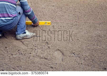 A Worker Leveling Land With A Level Ruler And Thread, Outdoor Shot