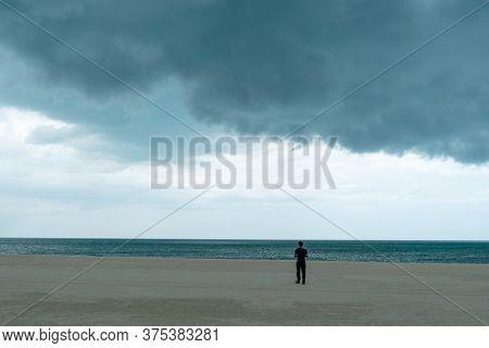 Man Standing In Beach With Dark Huge Cloud Sky Black Stormy Cloud Motion In Big Rain Day Thunderstor