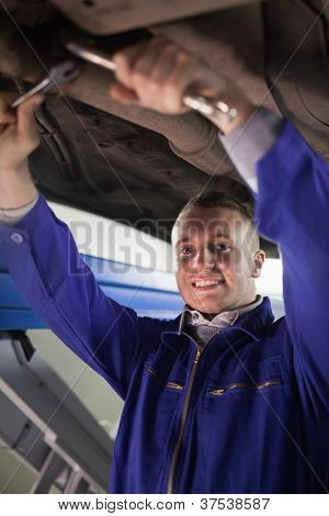 Mechanic repairing a car while looking at camera in a garage