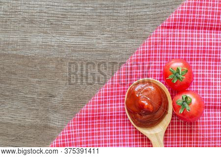 Tomato Ketchup Sauce In Wooden Spoon On Placemat With Tomatoes Over Wooden Background.