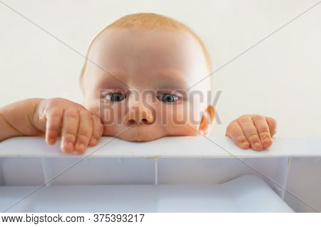 Cute Red-haired Hungry Baby Biting Plastic Board. Closeup View Of Curious Newborn Looking From Table