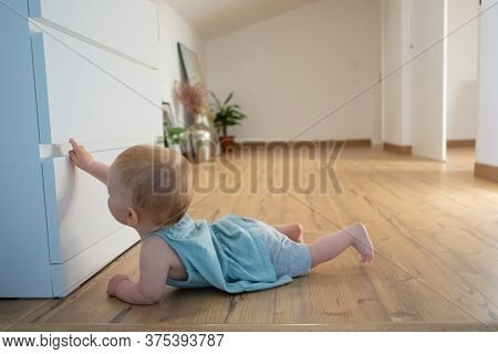Cute Newborn Touching Closed Wardrobe And Lying On Belly On Wooden Floor With Barefoot. Side View Of