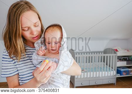 Focused Young Mom Holding Sweet Dry Baby Wrapped In Hooded Towel After Shower, Playing With Rubber B
