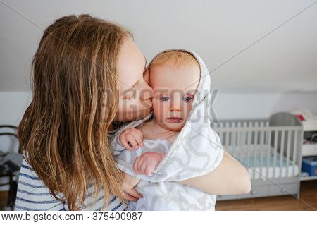 Young Mom Holding And Kissing Dry Baby Wearing Hooded Towel After Bathing Or Shower. Front View. Chi