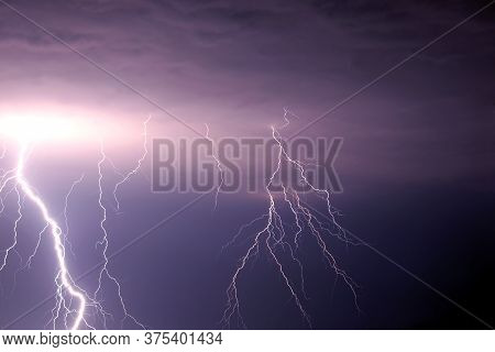 Many Bright Lightning Discharges In The Stormy Sky Under Heavy Purple Rain Clouds