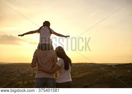 Back View Of Peaceful Family Watching Sunset At Mountains, Copy Space. Parents With Child Enjoying E
