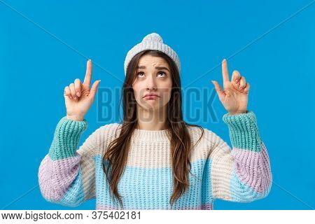Upset And Gloomy, Sulking Cute Caucasian Woman In Winter Hat, Sweater, Looking Pointing Fingers Up W