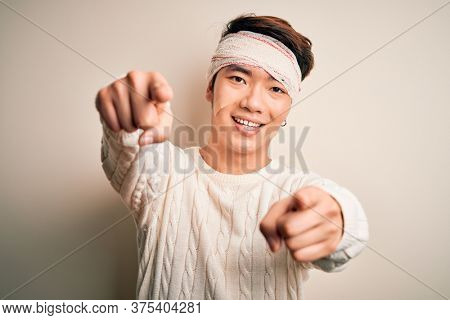 Young handsome chinese man injured for accident wearing bandage and strips on head pointing to you and the camera with fingers, smiling positive and cheerful