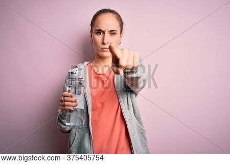 Young beautiful sporty woman doing sport drinking bottle with water to refreshment pointing with finger to the camera and to you, hand sign, positive and confident gesture from the front