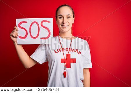 Lifeguard woman wearing t-shirt with red cross and whistle holding banner with sos message with a happy face standing and smiling with a confident smile showing teeth