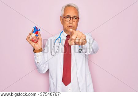 Middle age senior grey-haired cardiologist doctor man holding professional medicine heart pointing with finger to the camera and to you, hand sign, positive and confident gesture from the front