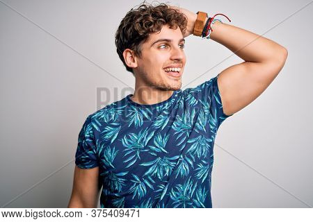 Young blond handsome man on vacation with curly hair wearing casual summer t-shirt smiling confident touching hair with hand up gesture, posing attractive and fashionable