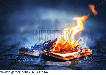 An Old Book Lies On A Rocky Path Made Of Cobblestones And Its Pages Burn With A Bright Strong Flame