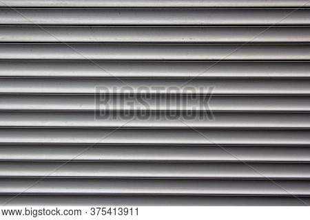 Background Of Grey Horizontal Metal Strips. Roller Blinds And Garage Gates. Closed Metal Shutter Cas
