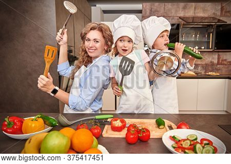 Funny children and their mother cook dinner together, they cut a salad of fresh vegetables. Happy family. Healthy eating.