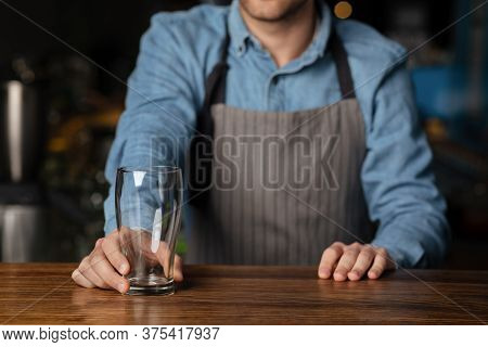 Customer Service In Pub. Barman In Apron Gives Empty Glass To Client On Wooden Bar Counter In Interi