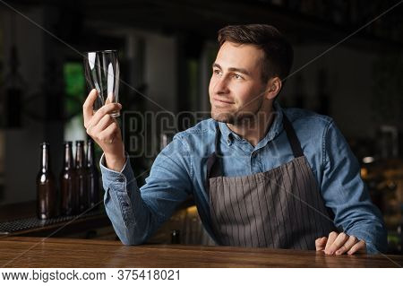 Check The Cleanliness Of Beer Glass. Satisfied Barman In Apron Looks At Empty Glass In Pub Interior