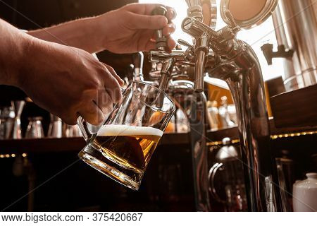 Bartenders Work . Bartender Pours Beer From Tap In Glass Mug In Interior Of Pub, Close Up, Cropped