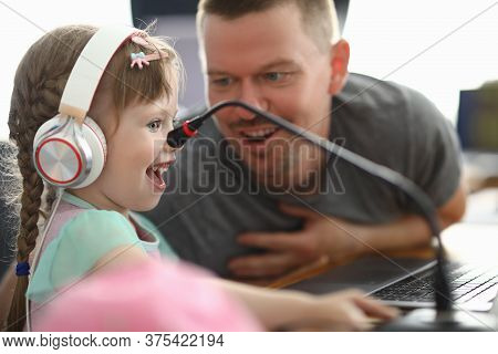 Little Happy Girl In Headphones Looks With Enthusiasm At Monitor Next To Man. Hanging Out Dad And Da